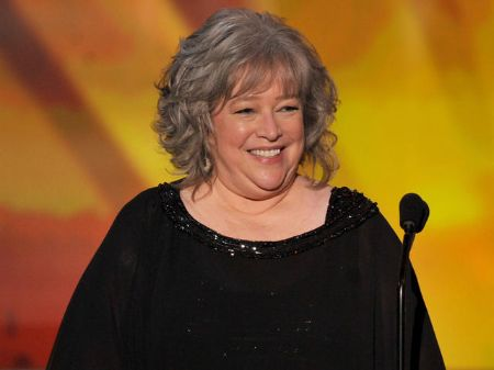 Kathy Bates, who underwent double mastectomy after breast cancer diagnosis, in front of a microphone.