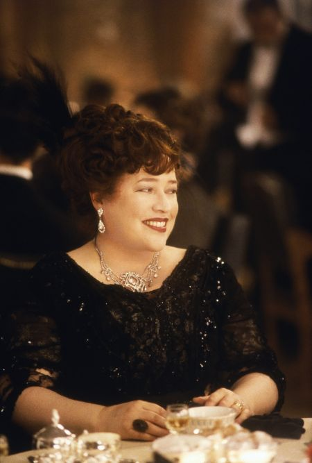 Kathy Bates portraying the role of Molly Brown in the film Titanic. She wears a classic black dress and looks quite young.
