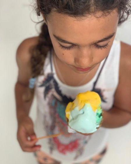 Matthew McConaughy and Camila Alves's cute daughter looks down at a yellow and blue ice cream.