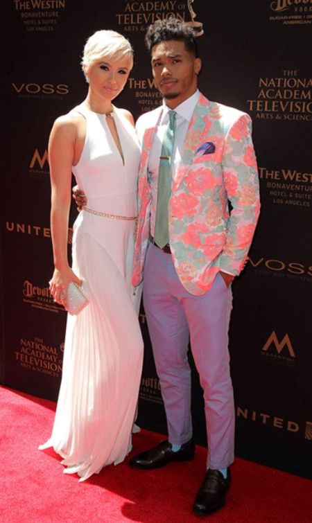 Rome Flynn wraps his arms around Camia Marie standing on the red carpet of the Daytime Emmy Awards in 2016. Camia looks stunning in a white dress whereas Rome sports a dashing pink flower blazer jacket.