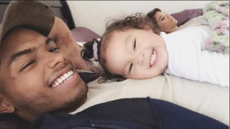 Rome Flynn with his daughter Kimiko Flynn resting on his chest. Both look very happy and are smiling.