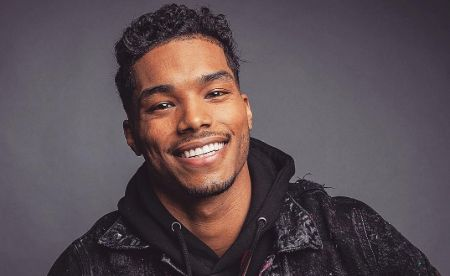 Rome Flynn cheerfully poses for the camera with a big smile.