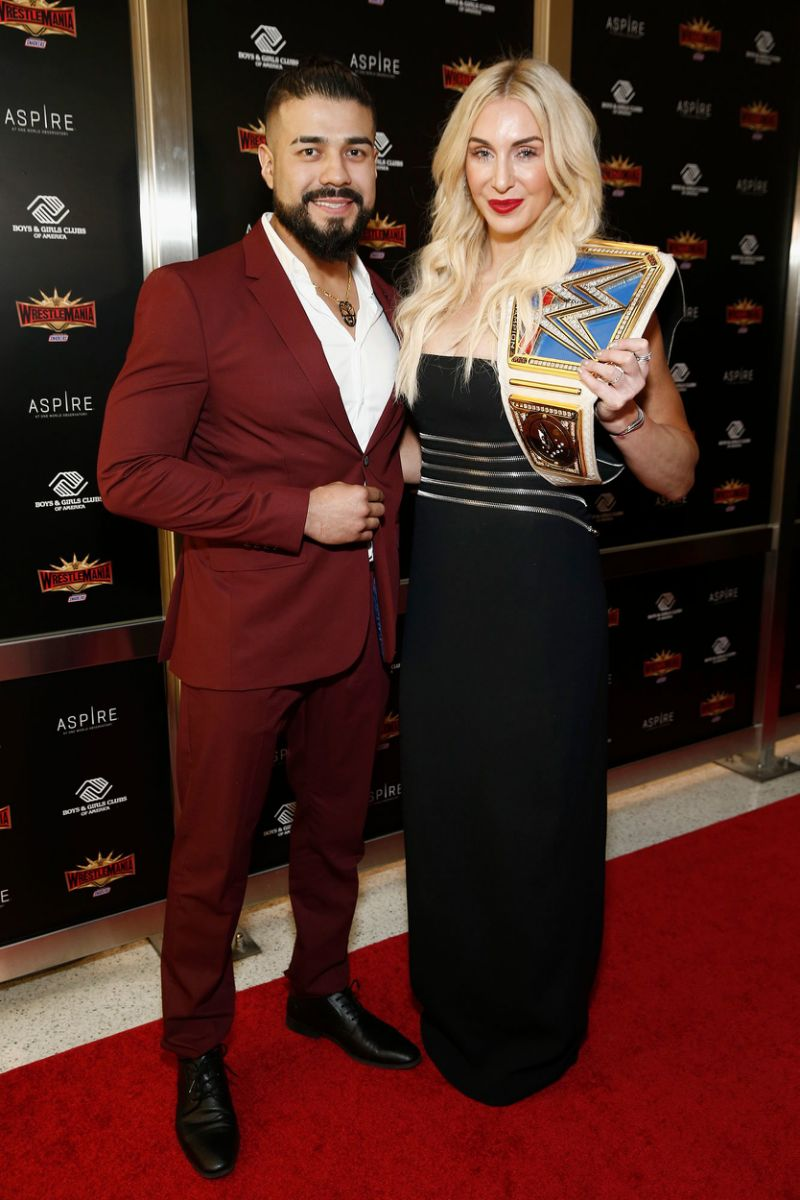 andreda in a maroon suit, charlotte in a black gown holding a wrestling belt award