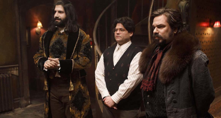 harvey standing in the middle to two guys, a scene from what do we do in the shadows