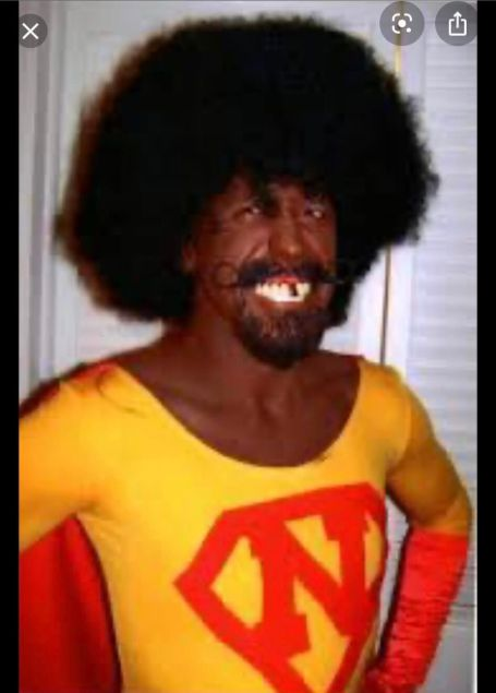 oliver with black face, afro , in a super hero costume with an N on his shirt