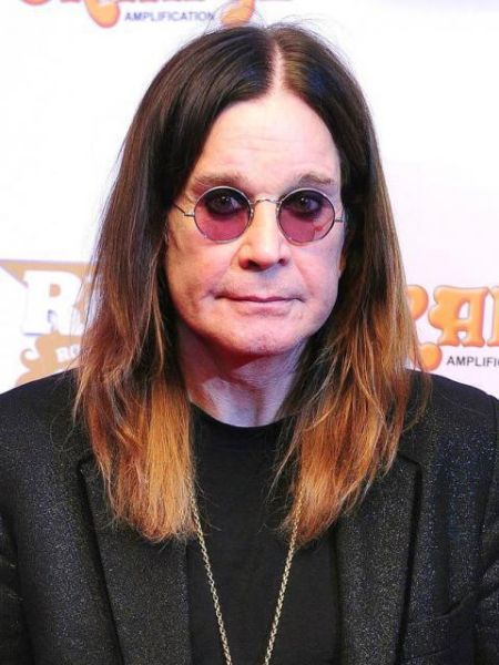 ozzy wearing a black coat, shoulder lenth dyed hair and round glasses