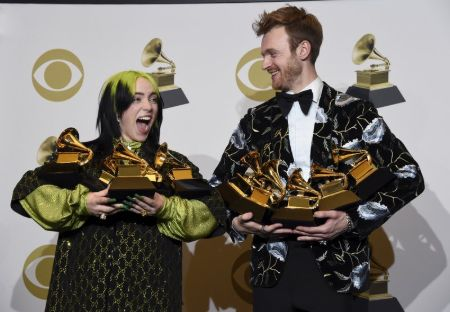 billie and brother Finneas holding 5 grammys each