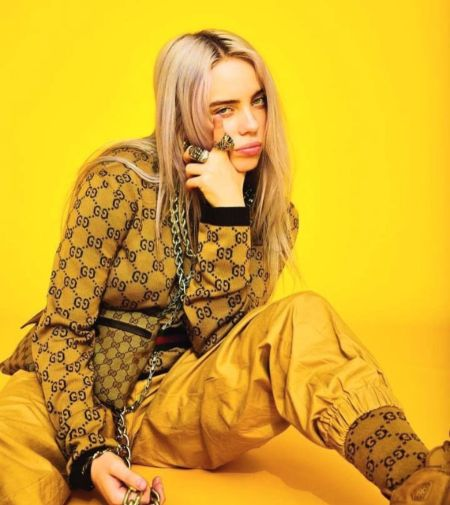 billie in all yello gucci outfit in a yellow back drop