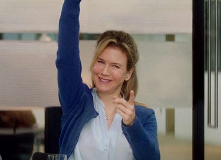Renée Zellweger raising her one hand and pointing the index finger of the other hand at the camera.