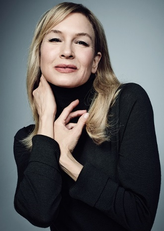 Renée Zellweger in a subtle pose wearing a black top with a smile.