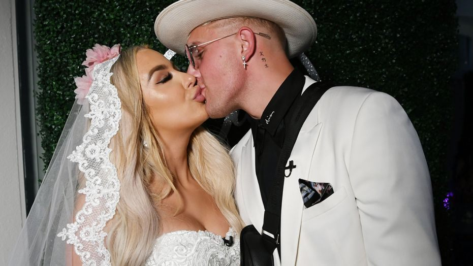 tana in a white wedding gown with jake in a white suit kissing on their wedding day