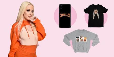 tana in an orange outfit along side her merch