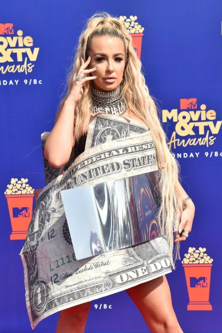tana mongeau in a dollar bill outfit with blonde hair posing with hands on her face