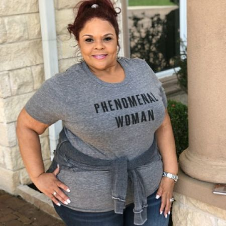 tamela in a grey shirt and pants with her hair up