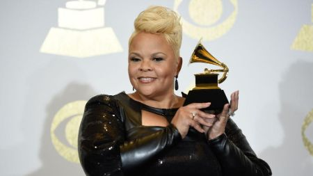 tamela in a black gown short blonde hair holding up her grammy award