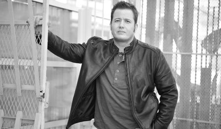 Chaz Bono in a black leather jacket poses for a picture.