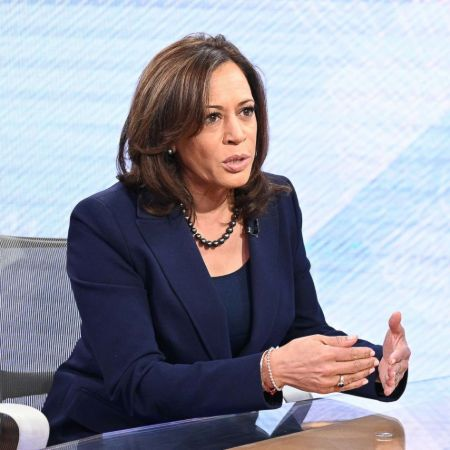 Kamala Harris in a black suit poses for a picture.