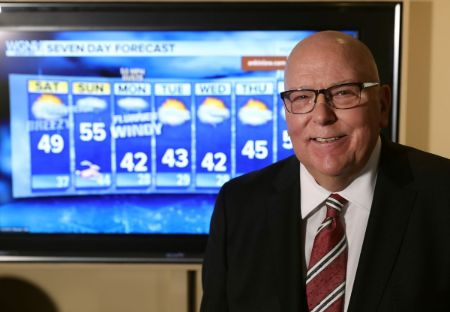 Tom Skilling in a black suit and red tie caught on the camera.
