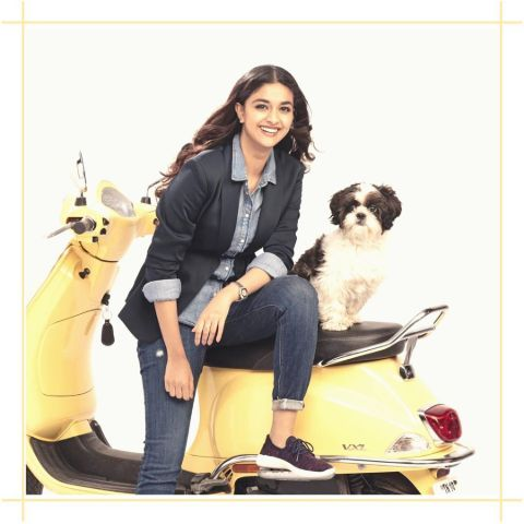 Keerthy Suresh in a black suit poses a picture with a dog in a photoshoot.