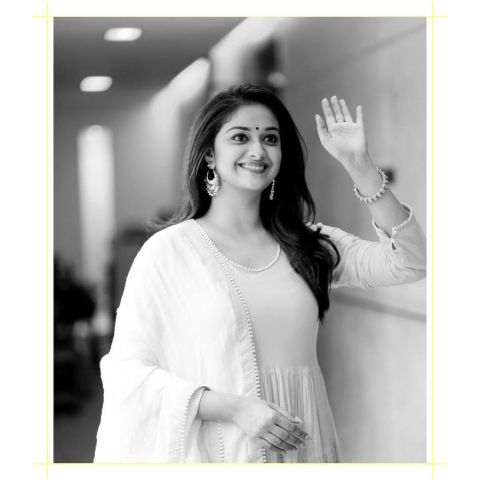 Keerthy Suresh in a white dress poses a picture.