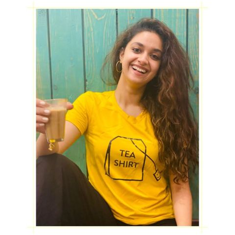 Keerthy Suresh in a yellow t-shirt poses a picture with a cup of tea.