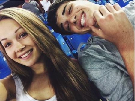 Noah Centineo in a grey t-shirt poses with former girlfriend Kelli Berglund at a baseball game.