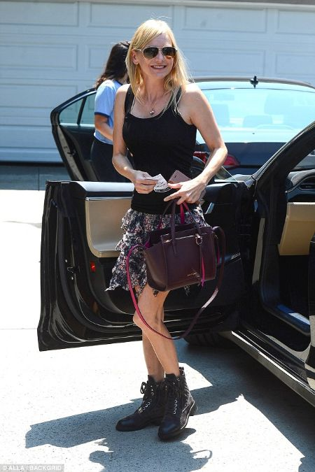 anna getting out of her car wearing ruffled skirt and black tank top
