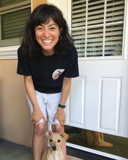 Melissa Villaseñor in a black t-shirt poses with her dog.
