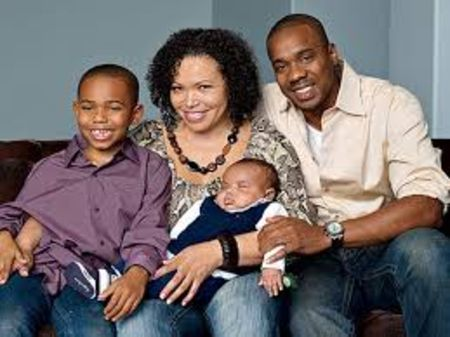 Tisha Campbell-Martin in a brown top with husband and two siblings.