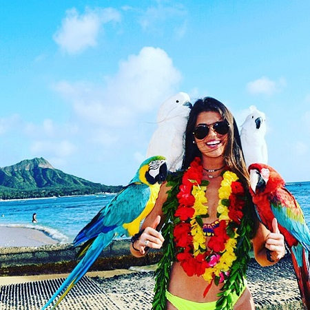 Madison Prewett with four birds on her hands and arms while vacationing in Hawaii.