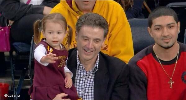Rick Pitino in a black coat holding her grand-daughter.