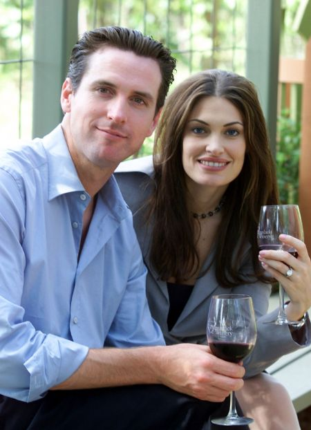 Kimberly Guilfoyle in a grey suit with ex-husband Gavin Newsom pose for a picture.