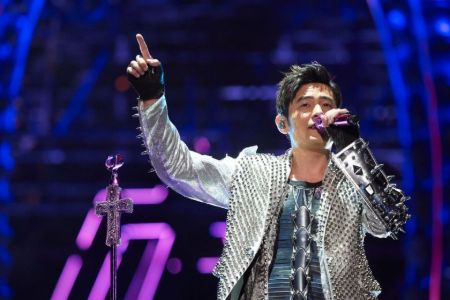 Jay Chou in a silver jacket singing a song.