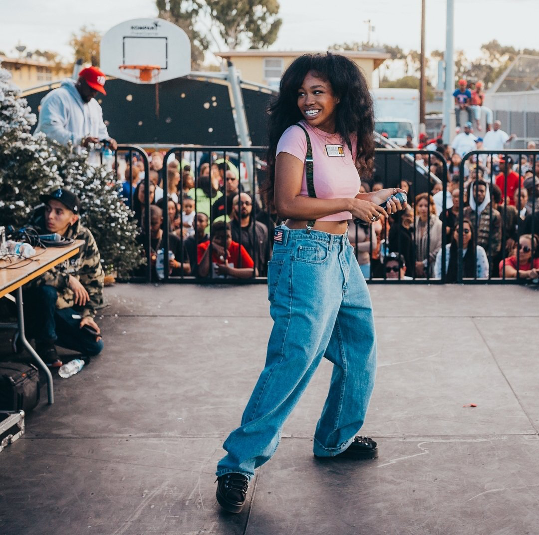 SZA wearing '90s baggy clothes while performing on stage.