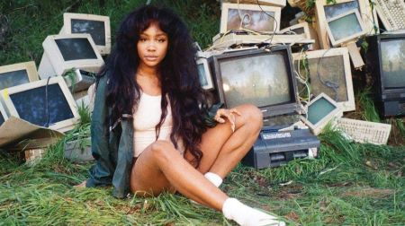 sza sitting on grass with broken old TVs and computers