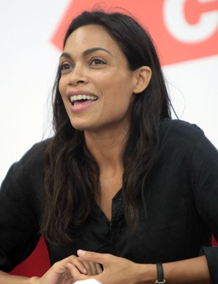 Rosario Dawson in a black top poses for a picture.