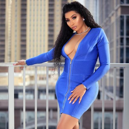 Karlie Redd in a blue dress poses for a picture.