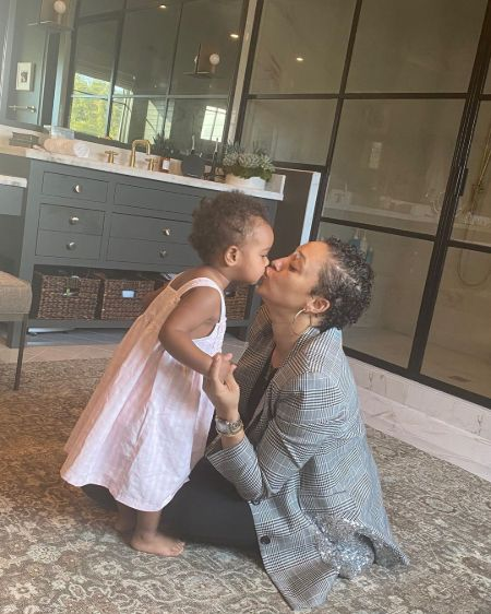 Tia Mowry in a grey sweater kisses her daughter.
