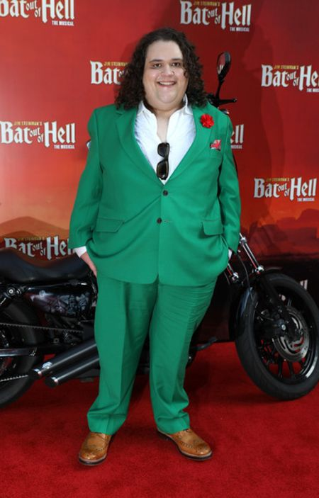 Jonathan Antoine  in a green suit poses at an event.