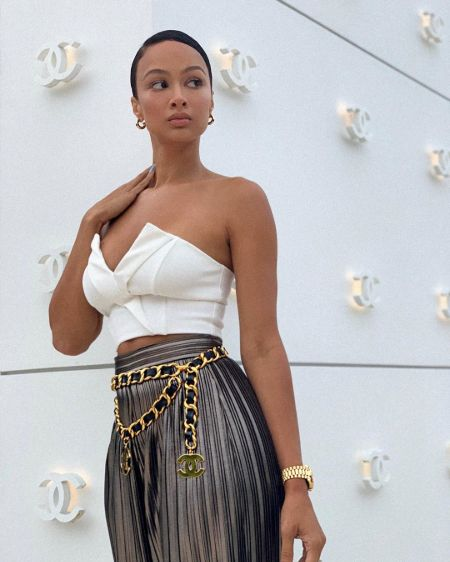 Draya Michele in a white top and black pants poses for a picture.