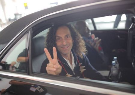 Kenny G in a black suit poses in his car.
