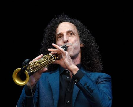 Kenny G in a blue suit playing a saxophone.