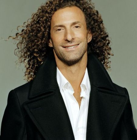 Kenny G in a black jacket poses for a picture.