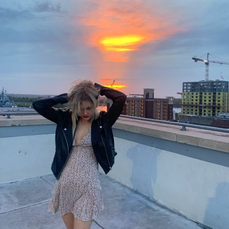 Emily Alyn Lind in a brown dress poses at the top of a building.