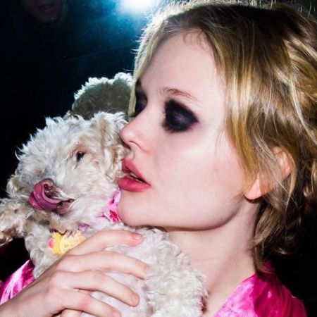 Emily Alyn Lind in a pink top hugs her puppy.