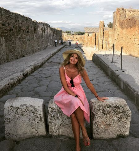 Paulina Porizkova in a pink dress wearing a hat poses for a picture at Pompel.