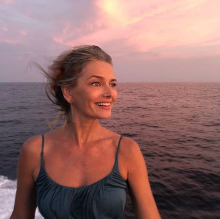 Paulina Porizkova in a blue top poses at a yacht at the middle of a ocean.