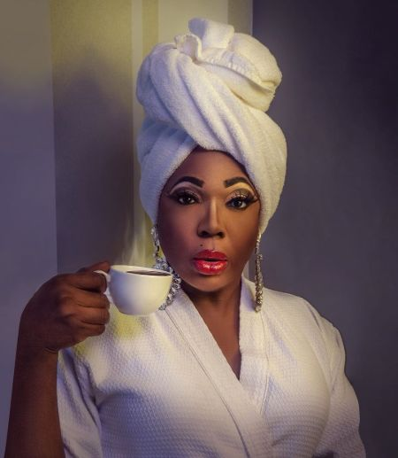 Dragnificent cast Bebe Zahara Benet in a gown drinking tea.