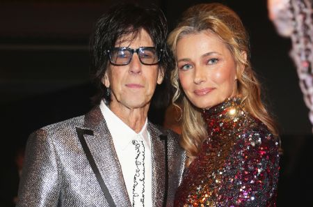 Paulina Porizkova in a red dress poses with her late-husband Ric Ocasek at an event.