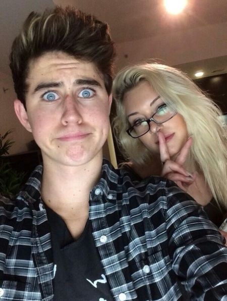 nash wearing a check shirt with stassie in the back wearing glasses with her finger on her lips